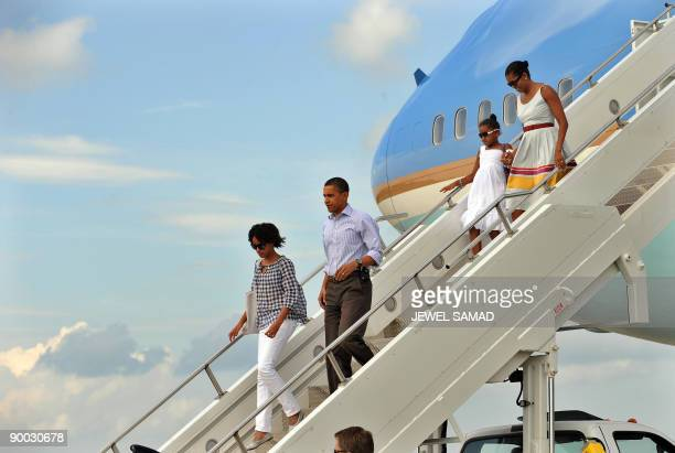 US President Barack Obama First Lady Michelle Obama and their daughters Malia and Sasha disembark from Air Force One at the Cape Cod Coast Guard Air...