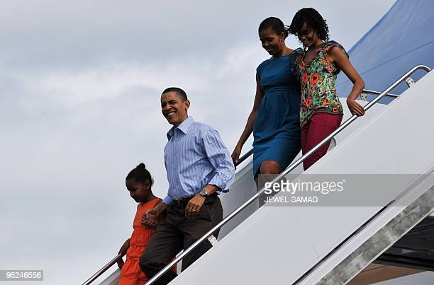 US President Barack Obama First Lady Michelle Obama and their daughters Malia and Sasha disembark from Air Force One upon their arrival at the Hickam...