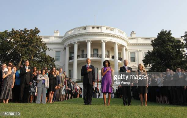 President Barack Obama, first lady Michelle Obama, Vice President Joseph Biden, his wife Jill Biden, and White House staff observe a moment of...