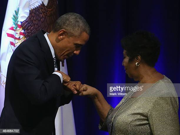 President Barack Obama fist bumps with singer Aretha Franklin who sung during a farwell ceremony for Attorney General Eric Holder at the Justice...