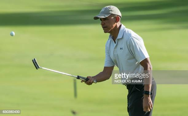 US President Barack Obama flips a golf ball with his putter while waiting to putt on the 18th green at the Kapolei Golf Club in Kapolei on December...