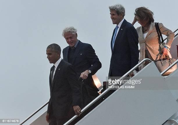 US President Barack Obama former president Bill Clinton Secretary of State John Kerry and House Minority Leader Nancy Pelosi walk off Air Force One...