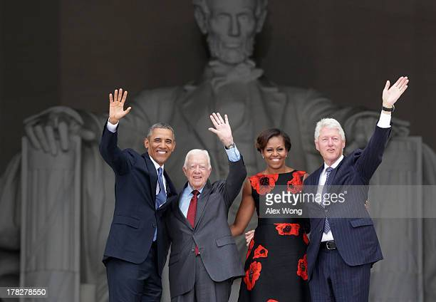 US President Barack Obama former president Jimmy Carter first lady Michelle Obama and former president Bill Clinton wave as they leave at the end of...