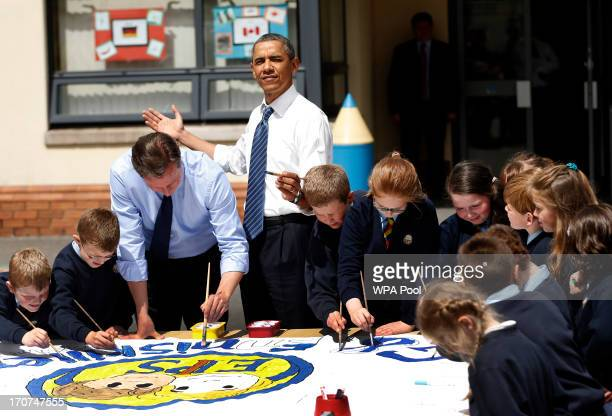 President Barack Obama fourth left reacts as the sun comes out as he works alongside British Prime Minister David Cameron third left helping students...