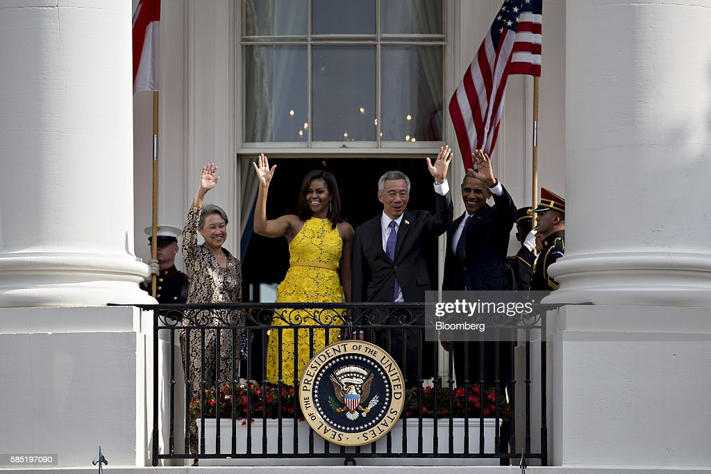 U.S. President Barack Obama, from right, Lee Hsien Loong, Singapore's prime minster, U.S. First Lady Michelle Obama and Ho Ching, wife of Lee Hsien Loong, wave from the Truman Balcony during an official arrival ceremony on the South Lawn of the White House in Washington, D.C., U.S., on Tuesday, Aug. 2, 2016. The occasion marks first official visit by a Singapore prime minister since 1985. Photographer: Andrew Harrer/Bloomberg via Getty Images