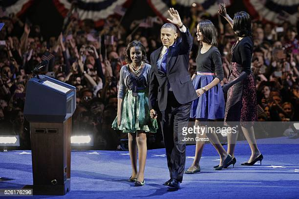 US President Barack Obama gathers with his wife Michelle Obama and daughters Sasha and Malia during his election night victory rally in Chicago...