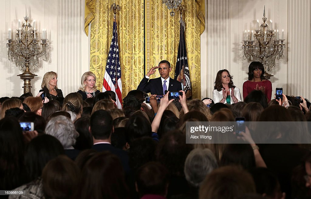 U.S. President Barack Obama (C) gestures as (L-R) Vice President Joseph Biden's wife Jill Biden, Catherine Russell, chief of staff to Jill Biden, Amanda McMillan of Mississippi, and first lady Michelle Obama listen during a Women's History Month Reception in the East Room of the White House March 18, 2013 in Washington, DC. President Obama delivered remarks in the event.