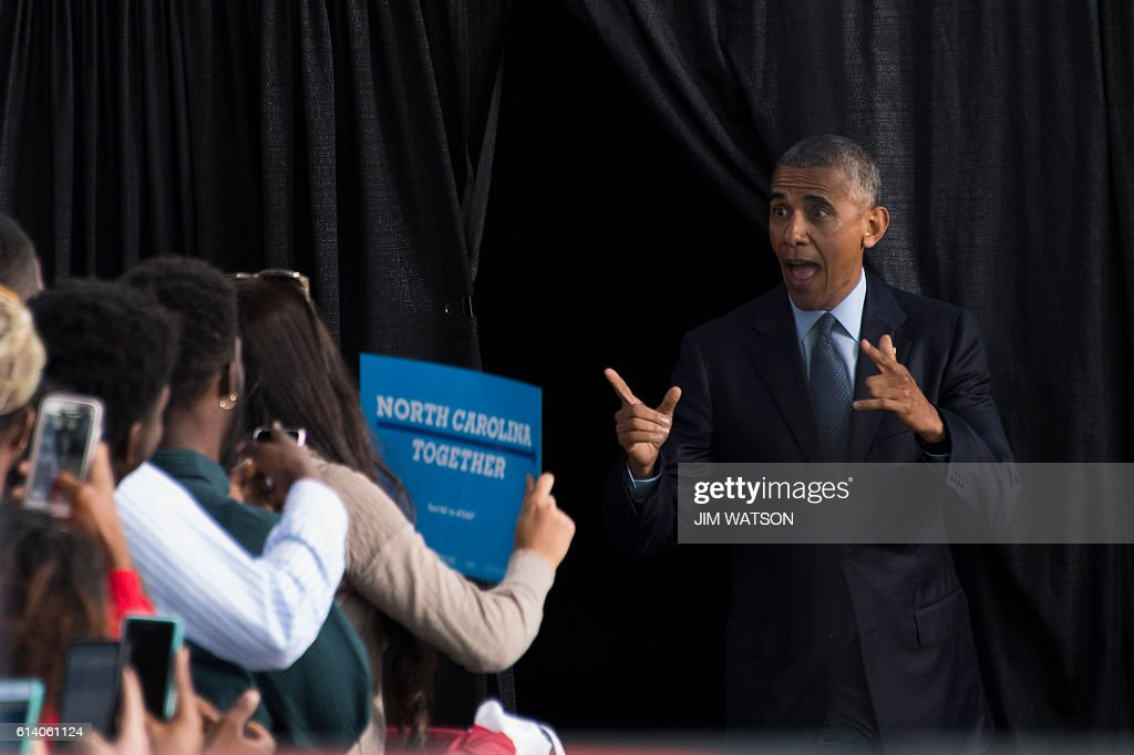 US President Barack Obama gestures at supporters as he arrives to speak during a Hillary for America campaign event in Greensboro, North Carolina, October 11, 2016. / AFP / JIM
