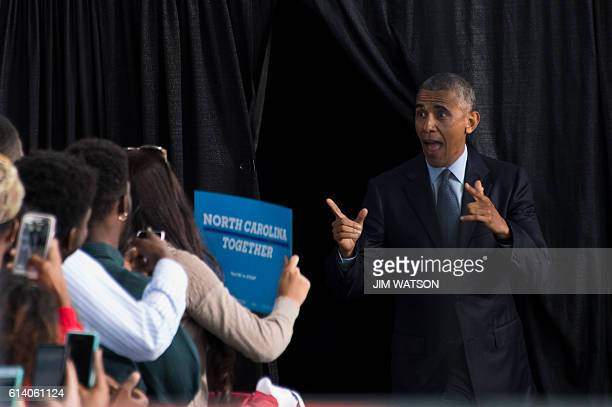 US President Barack Obama gestures at supporters as he arrives to speak during a Hillary for America campaign event in Greensboro North Carolina...