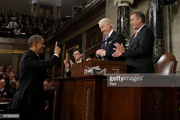 President Barack Obama gestures toward U.S. Vice President Joe Biden and House Speaker John Boehner before giving his State of the Union address...