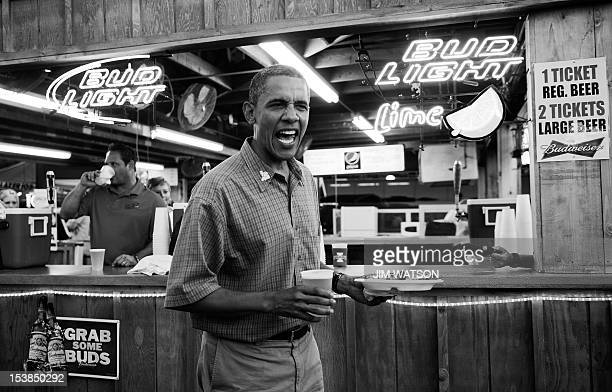 President Barack Obama gets a beer and a pork chop as he visits the Iowa State Fair in Des Moines Iowa on August 13 2012 during an unannounced stop...