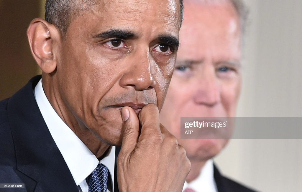 US President Barack Obama gets emotional as he speaks on reducing gun violence in the East Room of the White House on January 5, 2016 in Washington, DC. At right is US Vice President Joe Biden.