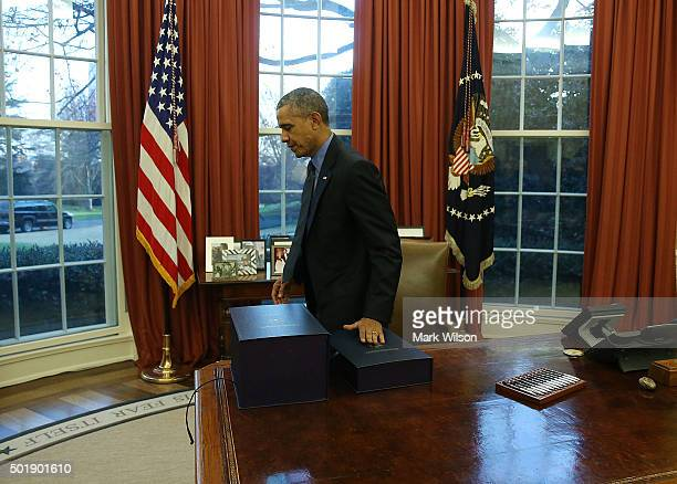 President Barack Obama gets up from his desk after signing the budget bill that will fund the government until next September in the Oval Office at...