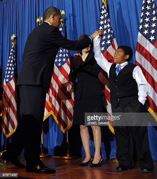 US President Barack Obama gives a 'high five' to 11 yearold Marcelas Owens after holding a rally celebrating the passage and signing into law of the...