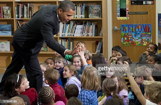 US President Barack Obama gives a highfive to a girl named Malia like his daughter after reading the book Twas the Night Before Christmas to students...