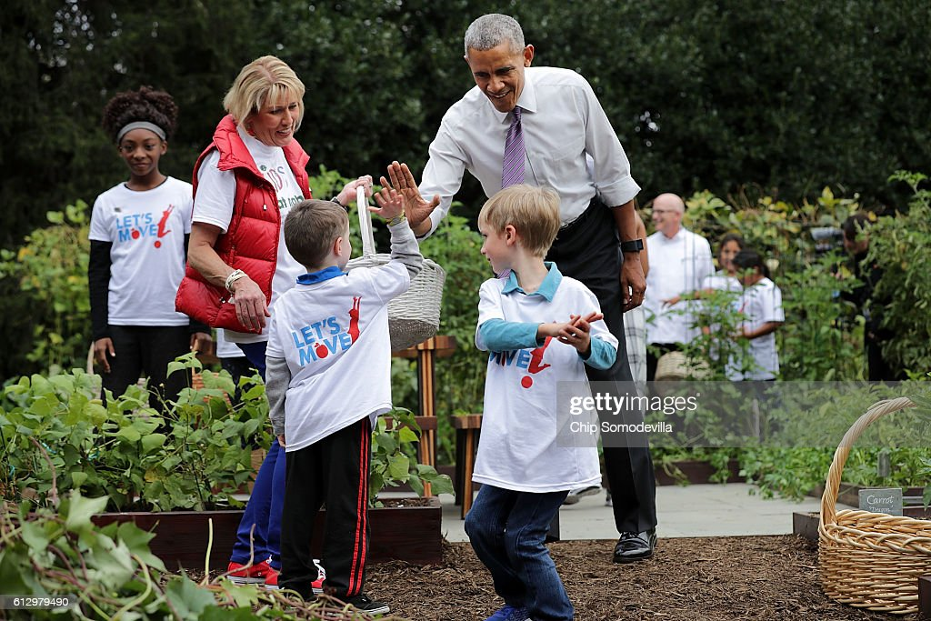 U.S. President Barack Obama gives a high-fives to students during an event to harvest the White House Kitchen Garden on the South Lawn of the White House October 6, 2016 in Washington, DC. Students from across the country were invited to help pull vegetables and greens from the garden which was established by first lady Michelle Obama in the spring of 2009. The garden is now a permanent feature on the White House grounds.