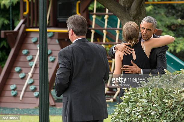 President Barack Obama gives a hug goodbye to Vice President Joe Biden's granddaughter Finnegan Biden before boarding Marine One on the South Lawn of...