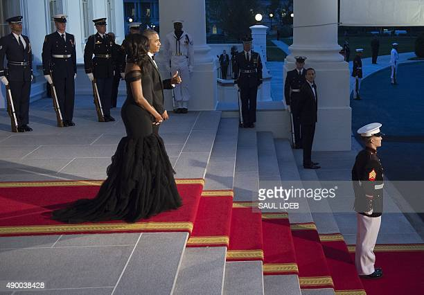 US President Barack Obama gives a thumbsup alongside First Lady Michelle Obama as they await the arrival of Chinese President Xi Jinping and his wife...
