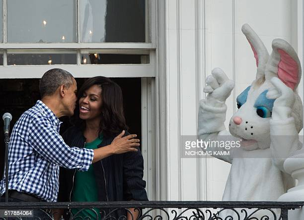 US President Barack Obama gives First Lady Michelle Obama a kiss as the Easter Bunny looks on at the annual Easter Egg Roll at the White House in...