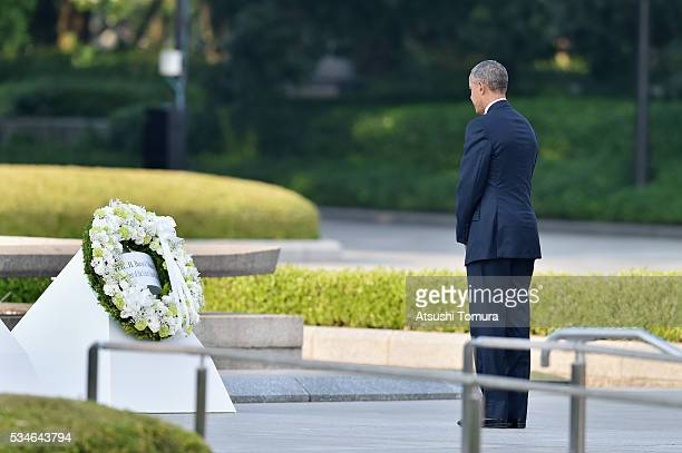 S President Barack Obama gives flowers during his visit to the Hiroshima Peace Memorial Park on May 27 2016 in Hiroshima Japan It is the first time...