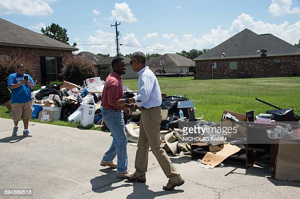 President Barack Obama greets a resident as he tours a flood-affected area in Baton Rouge, Louisiana, on August 23, 2016. President Barack Obama...