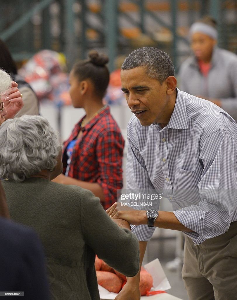 US President Barack Obama greets a woman as he distributes food items at the Capitol Area Food Bank on November 21, 2012, a day ahead of Thanksgiving, in Washington, DC. AFP PHOTO/Mandel NGAN
