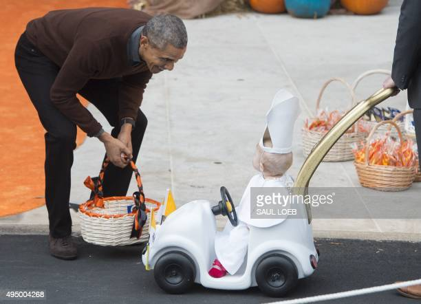 US President Barack Obama greets a young child dressed as the Pope and riding in a 'Popemobile' as he hands out treats to children trickortreating...