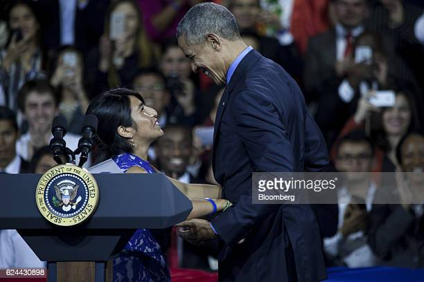 US President Barack Obama greets an attendee before speaking during a town hall meeting at the Pontifical Catholic University in Lima Peru on...