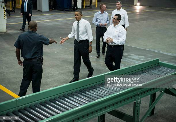 US President Barack Obama greets an employee while touring the Linamar factory February 13 2013 in Asheville North Carolina Obama toured the factory...