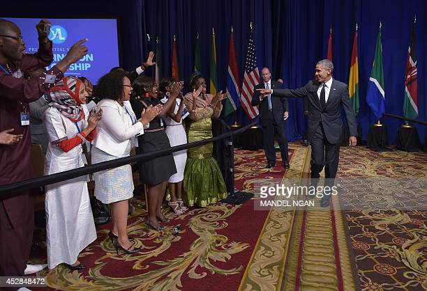 US President Barack Obama greets attendees as he arrive to speak at a town hall meeting at the Summit of the Washington Fellowship for the Young...