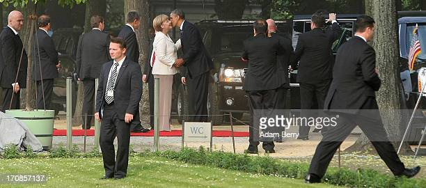 S President Barack Obama greets German Chancellor Angela Merkel amidst secret service officers and local security as they arrive for a dinner at the...