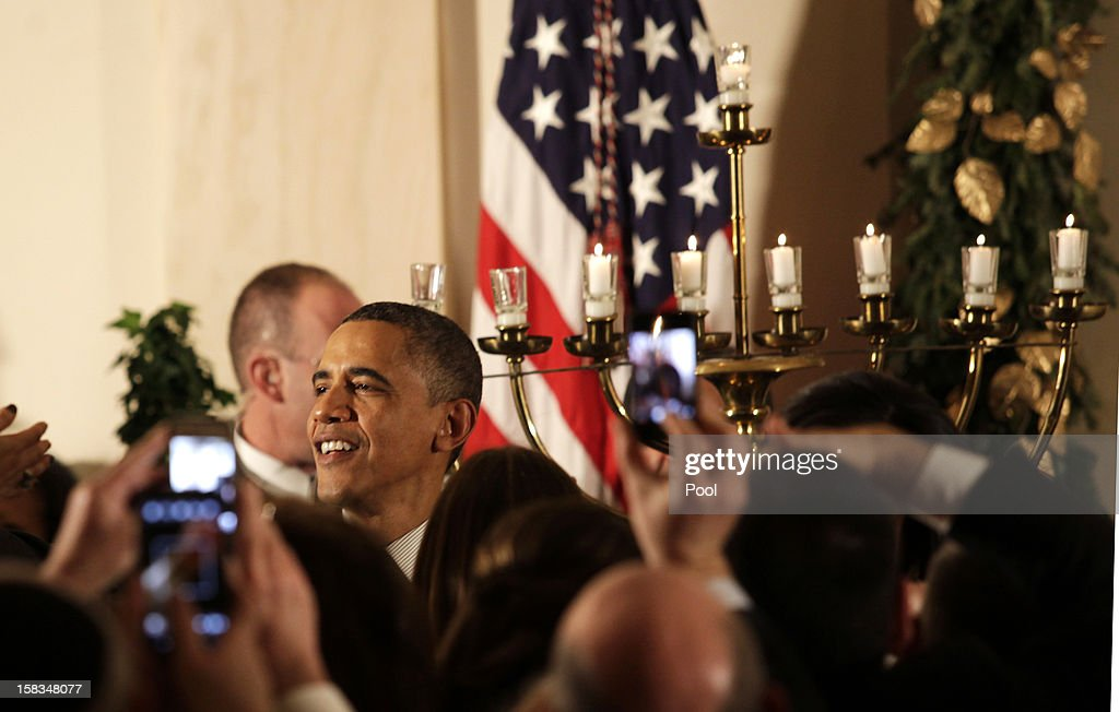 U.S. President Barack Obama greets guests following a Hanukkah reception in the Grand Foyer of the White House December 13, 2012 in Washington DC. The celebration included the lighting of candles in a 90-year-old menorah from a temple in Long Island, New York that was heavily flooded during Superstorm Sandy.