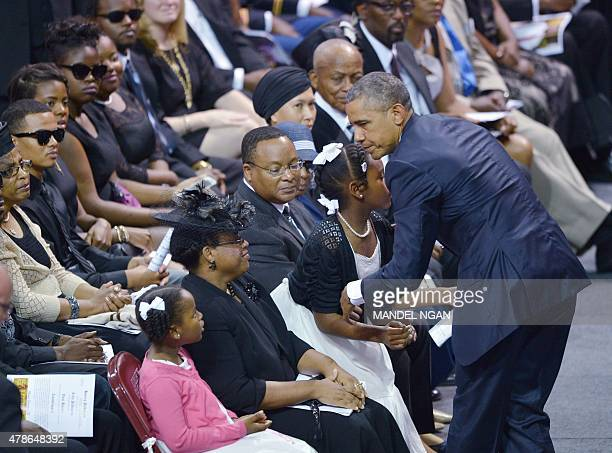 US President Barack Obama greets Malana and Eliana the daughters of Rev and South Carolina State Sen Clementa Pinckney as his wife Jennifer Pinckney...