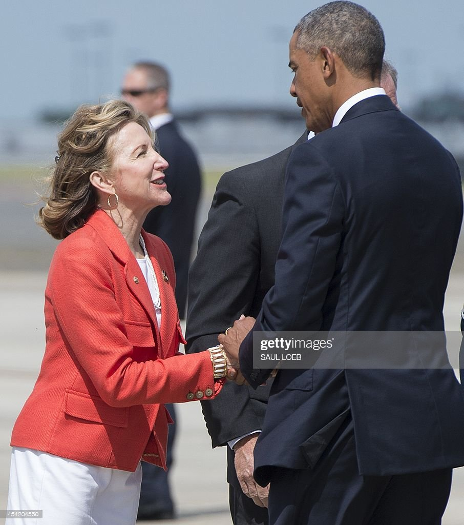 US President Barack Obama greets North Carolina Democratic Senator Kay Hagan upon arrival at Charlotte Douglas International Airport in Charlotte, North Carolina, August 26, 2014. Obama will speak at the American Legion's 96th National Convention. AFP PHOTO / Saul LOEB
