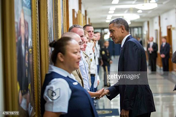 US President Barack Obama greets Pentagon employees after delivering remarks after a meeting with members of his national security team concerning...