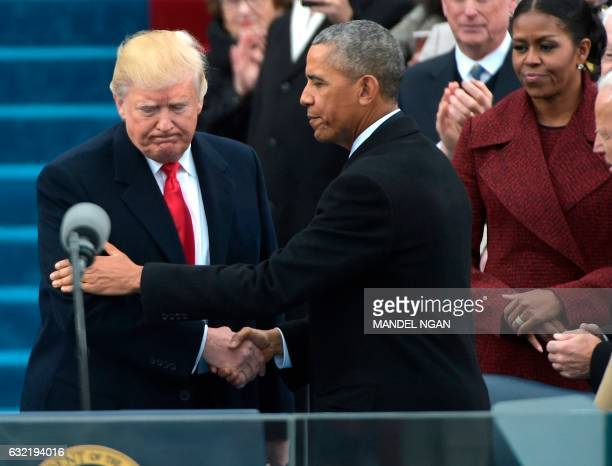 President Barack Obama greets Presidentelect Donald Trump as he arrives on the platform at the US Capitol in Washington DC on January 20 before his...