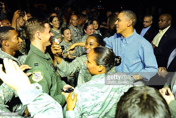 US President Barack Obama greets soldiers upon arriving at Joint Base Pearl HarborHickam in Honolulu Hawaii on December 20 2013 The First Family...