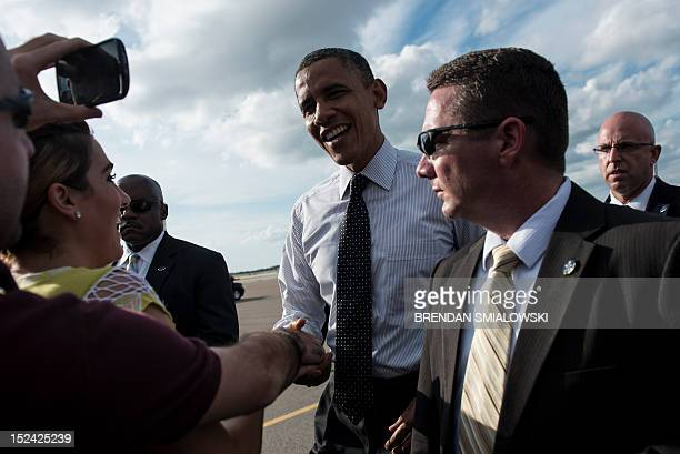 US President Barack Obama greets supporters after arriving at Tampa International Airport on September 20 2012 in Tampa Florida Obama is traveling in...