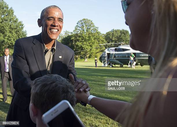 President Barack Obama greets the family of a Marine One crewmember upon arrival on the South Lawn of the White House in Washington, DC, August 23...