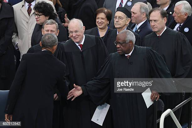 President Barack Obama greets the US Supreme Court Justices John Roberts Anthony Kennedy and Clarence Thomas on the West Front of the US Capitol on...