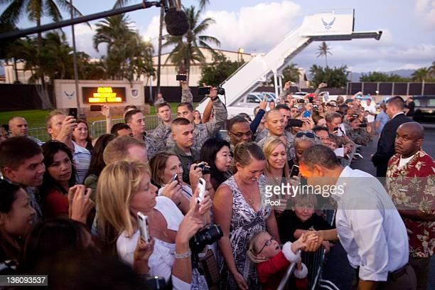 US President Barack Obama greets wellwishers after arriving at Joint Base Pearl HarborHickam December 23 2011 in Honolulu Hawaii President Obama...