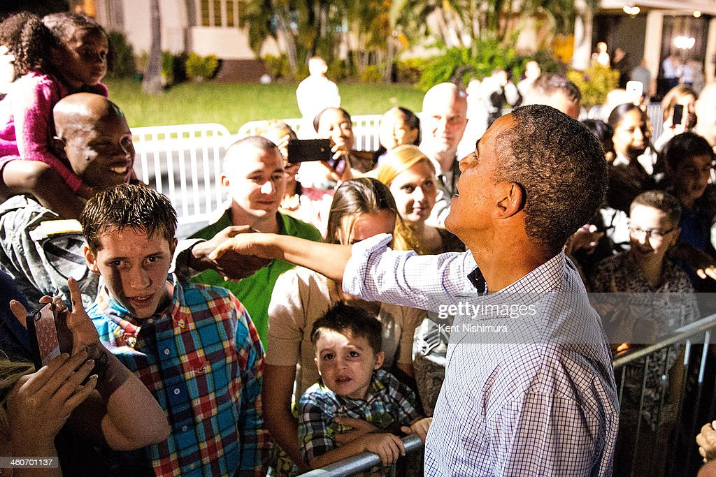 U.S. President Barack Obama greets well-wishers before boarding Air Force One on January 4, 2014 at Joint Base Pearl Harbor-Hickam in Honolulu, Hawaii. The President and daughters Sasha and Malia are returning to Washington, DC from Hawaii where they spent the winter holiday, while the First Lady is remaining in Hawaii.