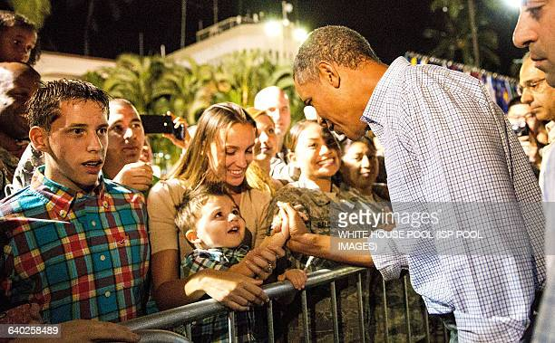 US President Barack Obama greets wellwishers before boarding Air Force One on January 4 2014 at Joint Base Pearl HarborHickam in Honolulu Hawaii The...