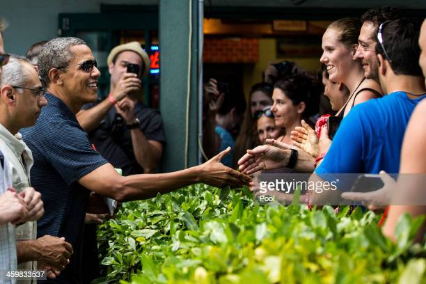 S President Barack Obama greets wellwishers outside of Island Snow at Kailua Beach Center on December 31 2013 in Honolulu Hawaii The First Family is...