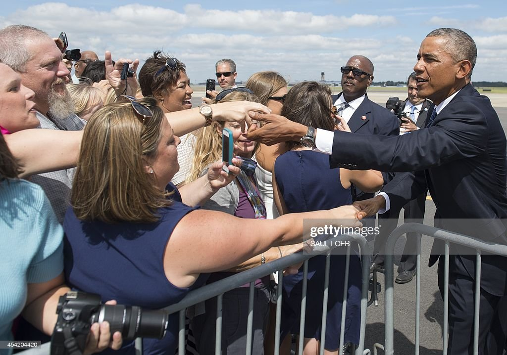 US President Barack Obama greets wellwishers upon arrival at Charlotte Douglas International Airport in Charlotte, North Carolina, August 26, 2014. Obama will speak at the American Legion's 96th National Convention. AFP PHOTO / Saul LOEB