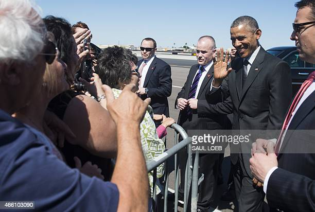 US President Barack Obama greets wellwishers upon arrival on Air Force One at Phoenix Sky Harbor International Airport in Phoenix Arizona March 13...