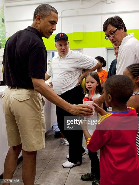 US President Barack Obama hands a Shave Ice to the child of a family friend at Island Snow at Kailua Beach Center on December 27 2010 in Kailua...