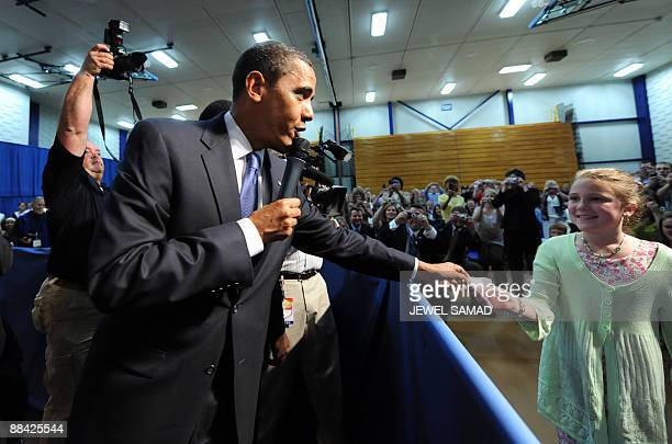 US President Barack Obama hands out a hand written excuse to a school girl for her teacher during a town hall meeting at the Southwest High School in...
