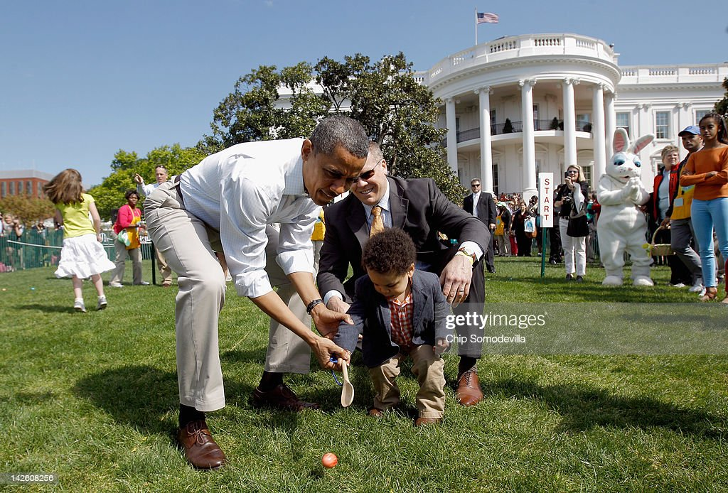 U.S. President Barack Obama (L) helps a young participant roll an egg during the White House Easter Egg Roll on the South Lawn of the White House on April 9, 2012 in Washington, DC. Thousands of people people are expected to attend the 134-year-old tradition of rolling colored eggs down the White House lawn that was started by President Rutherford B. Hayes in 1878.
