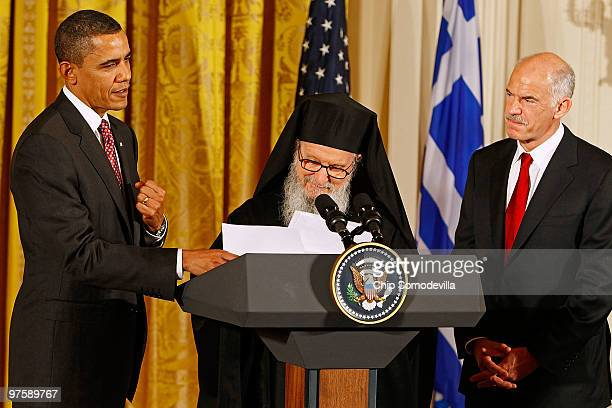 US President Barack Obama helps Archbishop Demetrios Primate of the Greek Orthodox Church in America with his notes as Greek Prime Minister George...